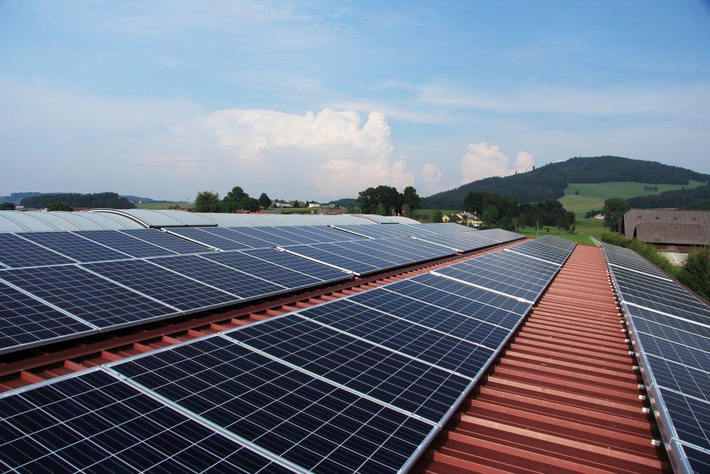 panele fotowoltaiczne zamontowane na dachy hali produkcyjnej